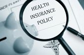 stock photo of insurance-policy  - Magnifying glass over health insurance policy and piggy bank - JPG
