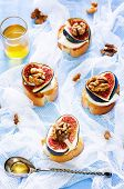 picture of walnut  - bruschetta with figs honey goat cheese and walnuts on a light background - JPG