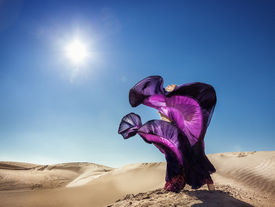 foto of barchan  - Woman in violet skirt dancing in the desert at blue sky - JPG