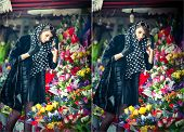 picture of flower shop  - Beautiful brunette woman with gloves choosing flowers at the florist shop - JPG
