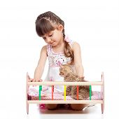 stock photo of baby doll  - Little girl playing with a kitten and rocking him in doll crib