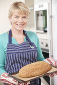 picture of home-made bread  - Woman In Kitchen Holding Tray With Home Made Loaf Of Bread - JPG