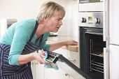 image of disappointed  - Frustrated Woman Looking In Oven With Disappointed Expression - JPG