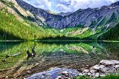 stock photo of avalanche  - gorgeous sunlit Avalanche lake with reflection in Glacier National Park - JPG