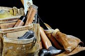 picture of leather tool  - Rugged worn carpenters leather work bags and belt with construction tools and hammer isolated on black and selective focus on leather texture - JPG