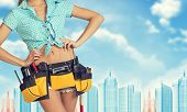 stock photo of framing a building  - Woman in tool belt with different tools stands back - JPG