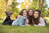 stock photo of bff  - Trio of happy teen girls laying down on grass - JPG
