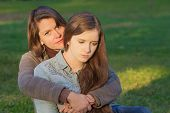 stock photo of depressed teen  - Concerned European mother holding depressed daughter outdoors - JPG