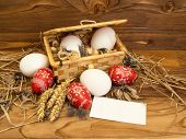 pic of wooden basket  - Easter chicken eggs in a basket on a wooden background - JPG