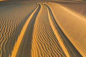 stock photo of four-wheel  - Four Wheel Drive car tire print on sand dune in the desert of Fayoum Egypt - JPG