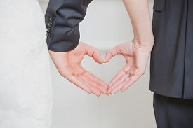 foto of marriage ceremony  - wedding couple showing shape of heart from their hands - JPG