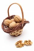 image of walnut  - Closeup of walnut without shell and stack of walnuts in wicker basket - JPG