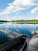 foto of bent over  - White clouds on the blue sky over blue lake with reflections with boats and boardwalk - JPG
