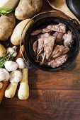 image of rutabaga  - Cast iron pot of bottled rabbit with vegetables laid our around the pot - JPG