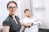 stock photo of psychologist  - Portrait of a beautiful woman psychologist wearing glasses and black blouse sitting at the light doctor office smiling holding some documents - JPG
