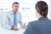 picture of conduction  - Businessman conducting an interview with businesswoman in an office - JPG