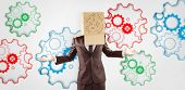 foto of anonymous  - Anonymous businessman with hands out against colourful cogs - JPG