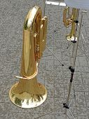 stock photo of aerophone  - Tuba and music stand with musical notation on the pavement in the rain - JPG