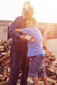 picture of grandfather  - Nephew huge grandfather outside in front of stack of wood - JPG