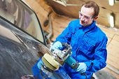 foto of car repair shop  - auto mechanic worker polishing car body at automobile repair and renew service station shop by power buffer machine - JPG