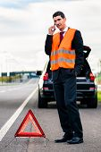 foto of erection  - Man with car breakdown erecting warning triangle on road - JPG