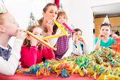 pic of blowing  - Children having birthday party with fun blowing streamers - JPG