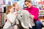 foto of stuffed animals  - family in toy store cuddling with stuffed animal - JPG