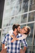 stock photo of piggyback ride  - Happy couple looking at each other while enjoying piggyback ride in city - JPG