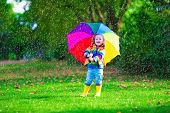 pic of rain  - Child with colorful umbrella playing in the rain - JPG