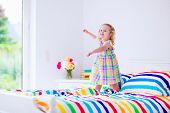 foto of little young child children girl toddler  - Children jump on a bed - JPG