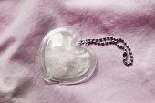picture of glass heart  - Glass heart on pink cotton cloth as a background - JPG