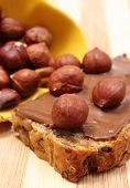 stock photo of hazelnut  - Closeup of hazelnut lying on slices of bread with chocolate cream heap of hazelnut in background - JPG