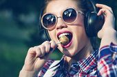 foto of lollipop  - Young hipster girl listening to music on headphones in a summer park - JPG