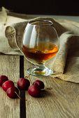 stock photo of black-cherry  - Brandy glass and black cherry vertical selective focus - JPG