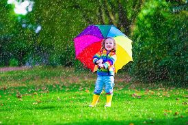 image of rainy weather  - Child with colorful umbrella playing in the rain - JPG
