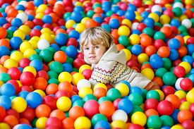 pic of pool ball  - Cute little toddler child playing at colorful plastic balls playground high view - JPG