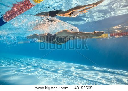 poster of Women swim in the swim pool outdoors. One girl swims in crawl style underwater. She wears a swimsuit, a swim cap and swim glasses. Her body reflected in water surface. Sunlight falls from above.