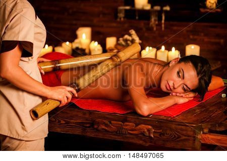 poster of Bamboo back massage. Young woman lying on wooden spa bed have bamboo massage therapy sticks. Bamboo
