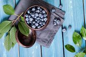 Freshly picked blueberries in metal bowl. Juicy and fresh blueberries with leaves on blue wooden tab poster