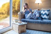 Young beautiful blonde woman with cup of coffee and book sitting home by the window. Autumn fall tre poster