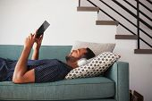Man Lying On Sofa At Home Wearing Headphones And Watching Movie On Digital Tablet poster