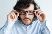 Surprised Black-haired Young Man Staring At Camera Through Glasses. Attractive Guy Adjusting Glasses poster