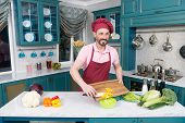 Bearded Cook In Apron And Cap Cutting Yellow Paprika. Smiling Guy In Cap Makes Salad With Paprika. C poster