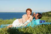 Attractive Couple Have A Rest In The Grass Near Of Big Lake. Loving Couple In Summer Day. Happy Lyin poster
