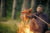 Camping Fire. Sausages Roasted On Bonfire Flame With Blurred Man Hipster On Natural Background. Picn poster