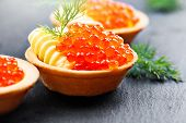 Tartlets with red caviar close up. Gourmet food close up, appetizer. Close-up salmon caviar. Delicat poster