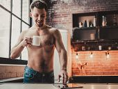Bare-chested Man With Tablet Pc And Drink Coffee In Kitchen. Man With Bare Torso. Using Portable Dig poster