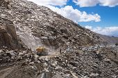 Indian Workers In Himalayas Mountain Work On The Road. Heavy Machinery Put Away Rocks. Very Difficul poster