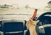 A Driver Holding Alcoholic Bottle While Driving / Drunk Driving Concept poster