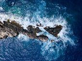 Aerial above waves crashing along rugged rocky coastline in mediterranean sea poster